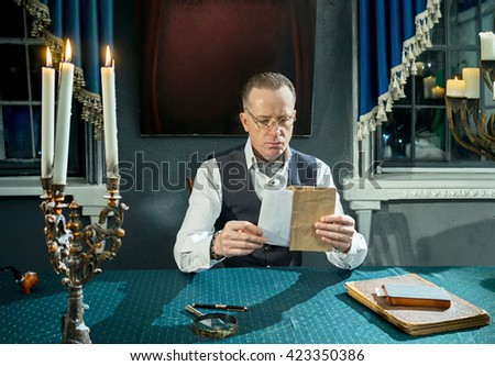 Man with a letter and envelope in hands at the table in his study