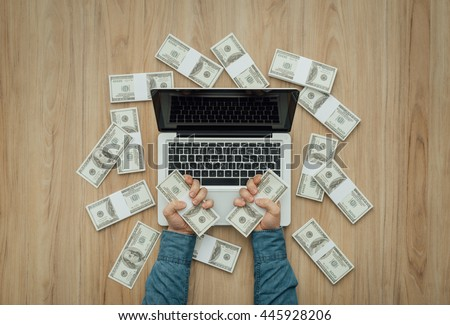 Man with a load of cash money using a laptop: winning, earning and earning concept - stock photo
