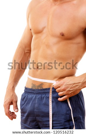 man with a muscular body measuring his abs - stock photo