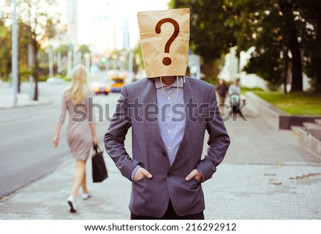 Man with a paper bag on head in the street - stock photo