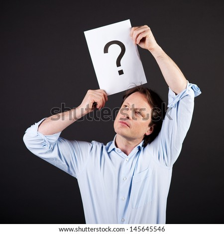 Man with a question mark drawn on a sheet of paper holding it above his head with a thoughtful expression on a dark background - stock photo