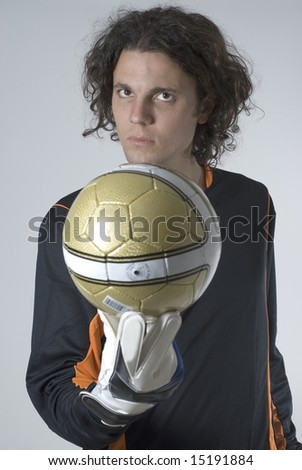 Man with a serious expression holds a soccer ball out in front of him. Vertically framed photograph. - stock photo