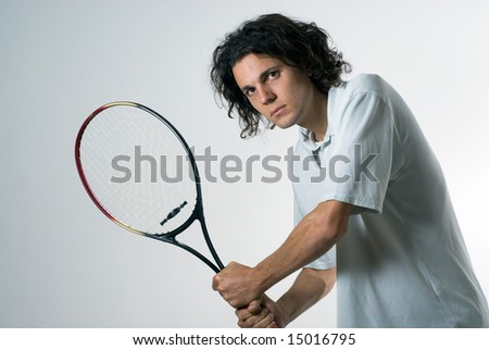 Man with a serious look on his face holds a tennis racket. Horizontally framed photograph