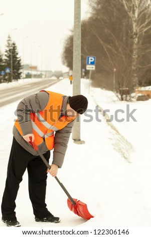 Man with a snow shovel clean the sidewalk - stock photo