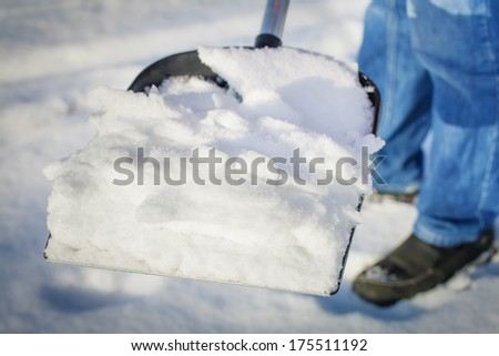 Man with a snow shovel in the hands of - stock photo