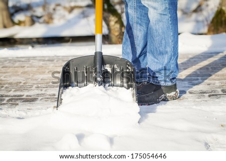 Man with a snow shovel on the sidewalk - stock photo