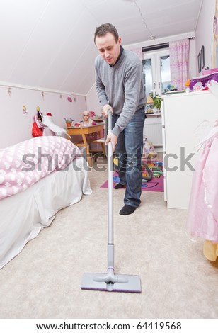 Man with a vacuum cleaner in a girls room - stock photo