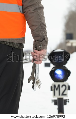 Man with adjustable wrench in the hand on the railroad - stock photo