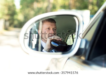 Man with alcohol behind the wheel of the car in the mirror - stock photo