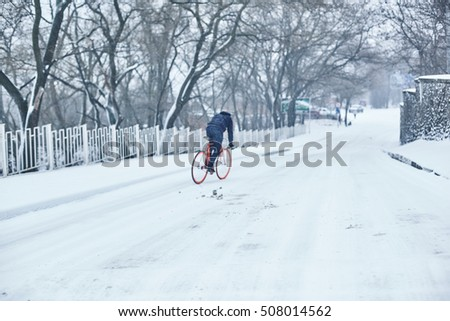 man with an orange bike in the winter
