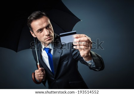Man with an umbrella and a credit card - stock photo