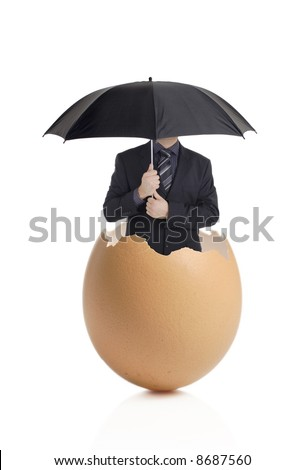 Man with an umbrella hatching out of an eggshell - stock photo