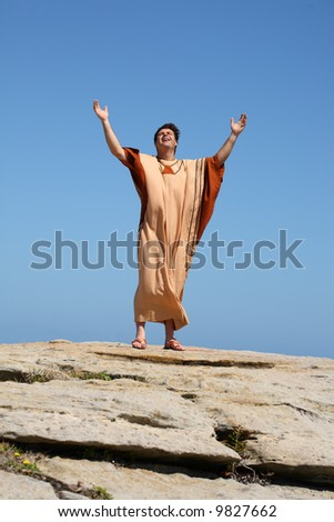 Man with arms raised to the sky in worship - stock photo