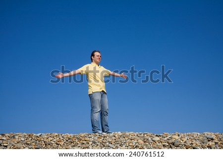 man with arms wide open at the beach - stock photo
