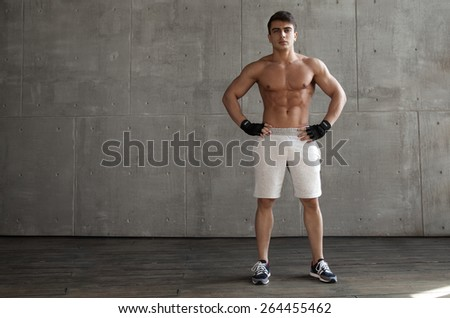 Man with athletic body poses for the camera background to the concrete wall - stock photo