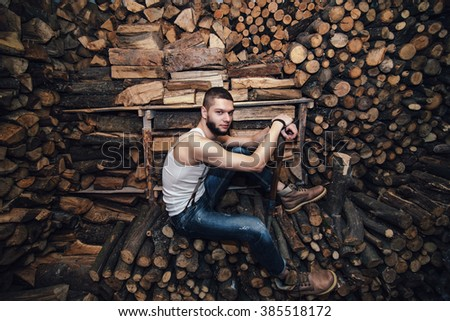 Man with ax in hands near firewood stock - stock photo