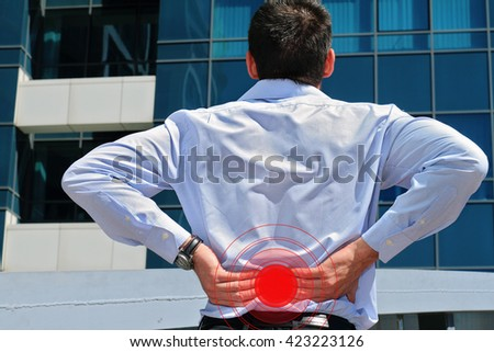 Man with back pain. Business man holding his lower back. Pain relief concept  - stock photo