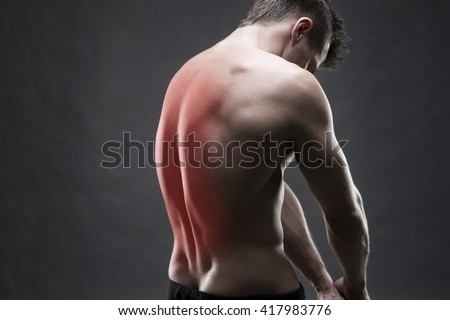 Man with backache. Pain in the human body. Muscular male body. Handsome bodybuilder posing on gray background with red dot - stock photo