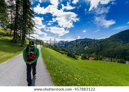man with backpac hiking on mountain trail in a sunny day