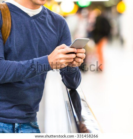 Man with backpack holding cell phone at airport waiting the flight - stock photo