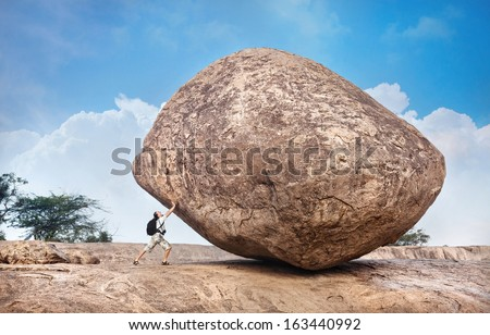 Man with backpack pushing a huge stone in Mamallapuram cave complex, Tamil Nadu, India - stock photo