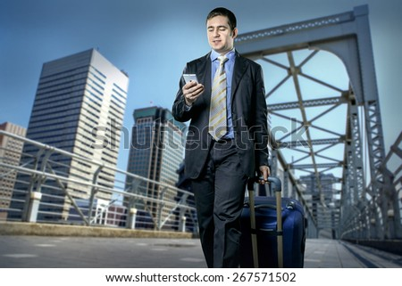 Man with baggage speaking by phone on the bridge - stock photo