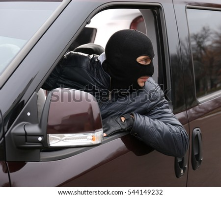 Man with balaclava on head trying to steal car