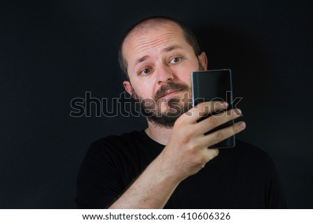 Man with beard and mustaches on black background in low key, holding smart phone and taking selfie - stock photo