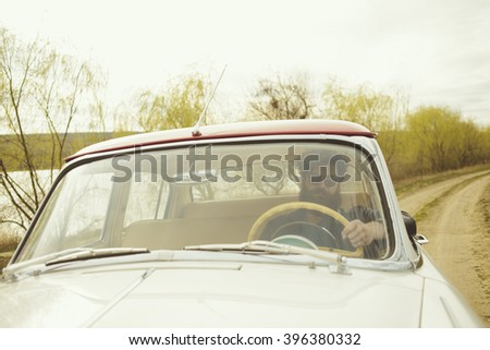 Man with beard driving a retro car