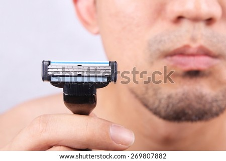 Man with beard holding up shaver - stock photo