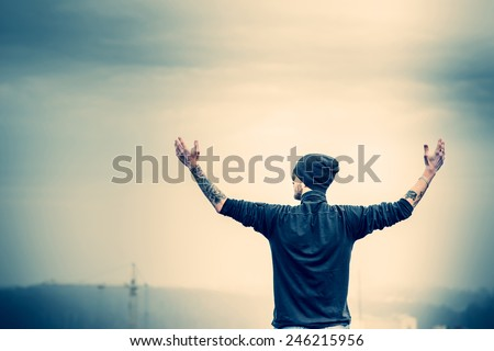 Man with beard on the top of the high building with cityscape on background - stock photo