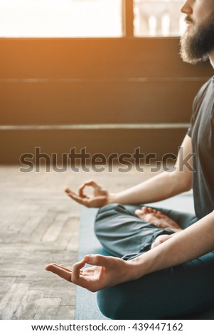 Man with beard wearing black T-shirt and trousers sitting in lotus asana, position of fingers in mudra, yoga position, copy space, portrait. - stock photo