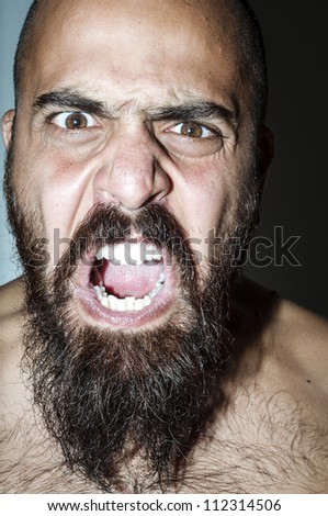 Man with beard with frightening expressions of anger
