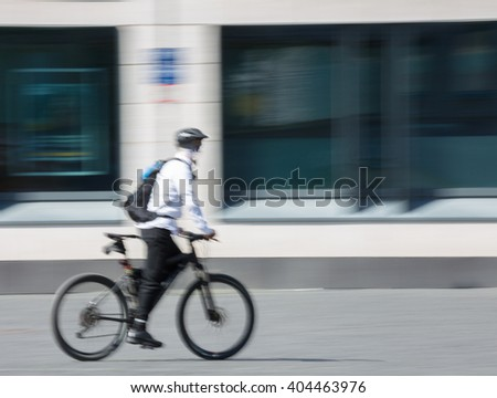 man with bicycle in the city, blurred, moving with Copy Space - stock photo