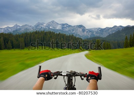 Man with bicycle riding mountain road - stock photo