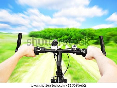 Man with bicycle riding on country road