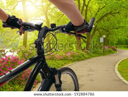 Man with bicycle riding spring park - stock photo