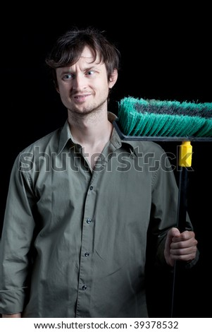 Man with big broom frowning at the mess he has to clean up - stock photo