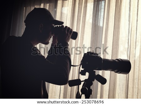 man with binoculars and camera control someone