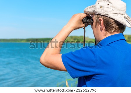 man with binoculars looks for something on the lake - stock photo