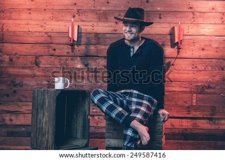 Man with blonde hair and brown cowboy hat wearing winter sleepwear. Sitting on wooden box inside cabin. - stock photo