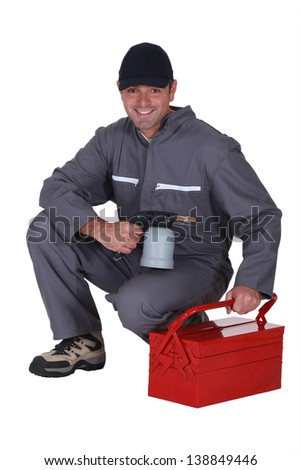 Man with blow-torch kneeling by tool kit - stock photo