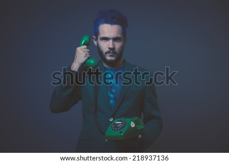 Man with blue hair and brown beard wearing green suit. Calling with vintage telephone. Male fashion. Studio shot against dark background. - stock photo