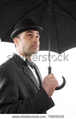 man with bowler hat and an umbrella