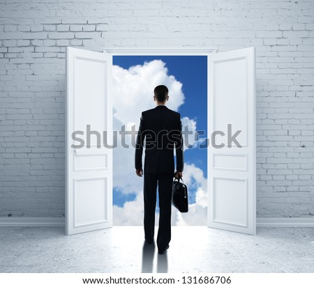 man with briefcase open door to blue sky - stock photo