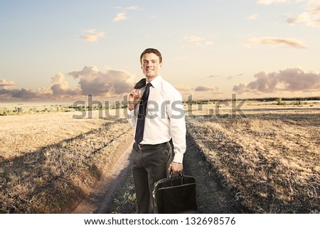 man with briefcase standing on a country road