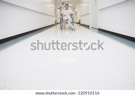 Man with broken leg in wheelchair at hospital - stock photo