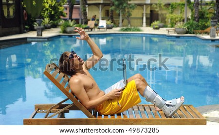 Man with broken leg is in pain poolside - stock photo
