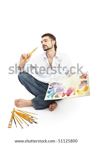 Man with brushes and palette  sitting.  Isolated over white - stock photo