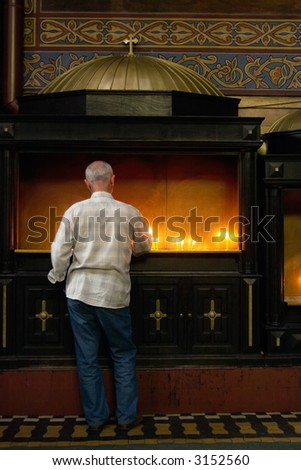 man with burning candle in catholic church - stock photo